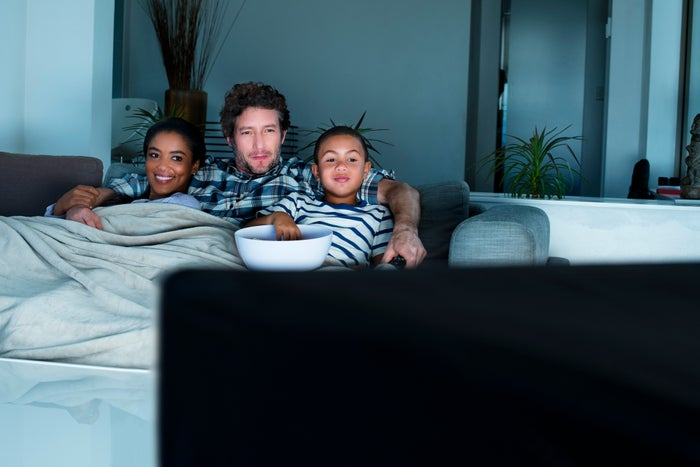 A young family gathered together on a couch, watching TV and eating a snack from a bowl.