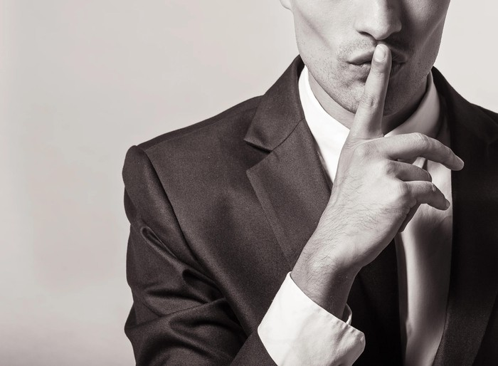 Person in suit with finger over his lips signaling 'Keep quiet.'