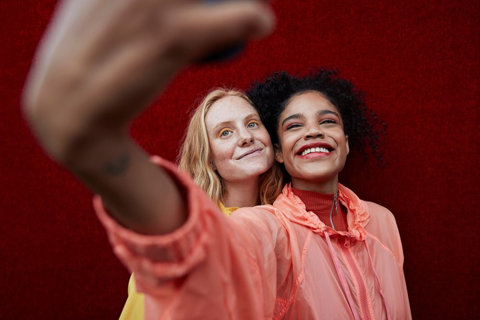 Two women take a selfie against a red wall.