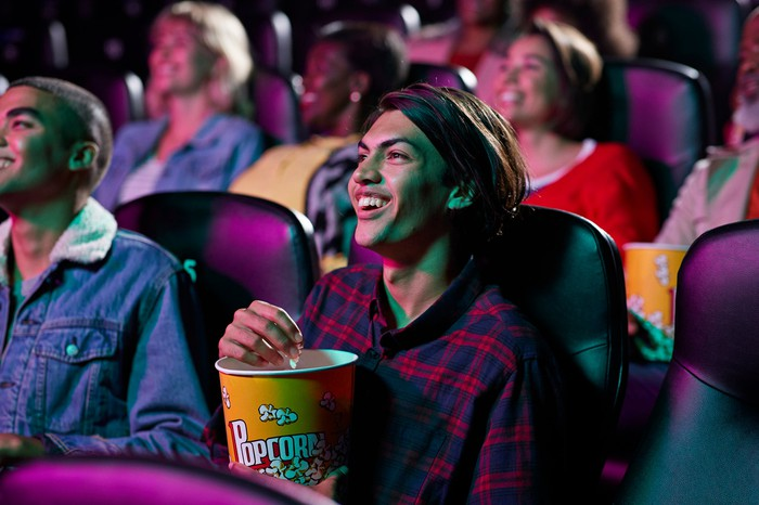 People eating popcorn and watching a film in a crowded movie theater.