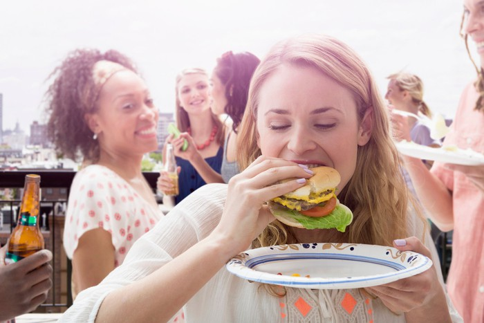 Friends stand on a deck smiling and eating veggie burgers.