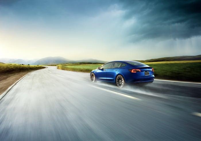 A blue Tesla Model 3 on the highway