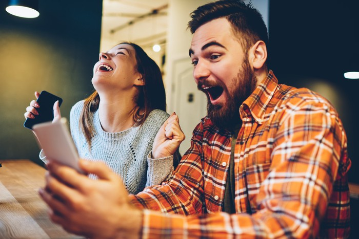 Man and woman cheering looking at smartphones