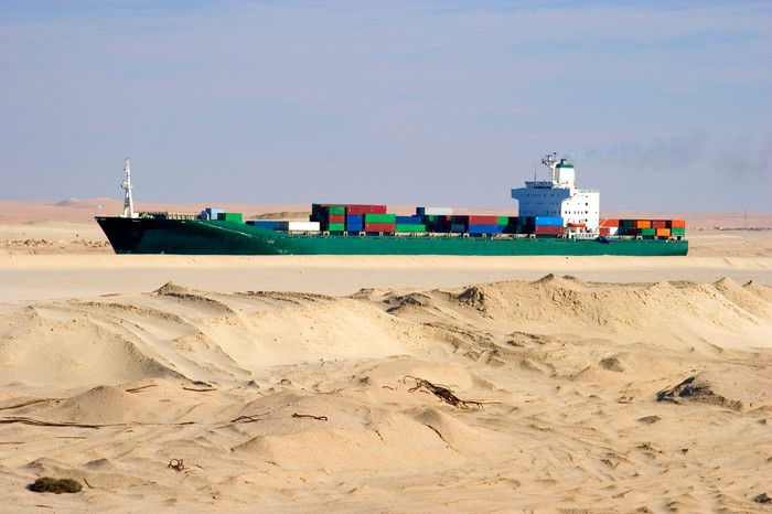 In an optical illusion, a containership looks like it's in a desert, but it's actually transiting the Suez Canal.