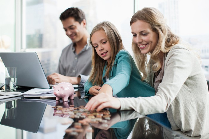 A mother and her daughter count coins in front of a piggy bank while a father consults a computer in the background.