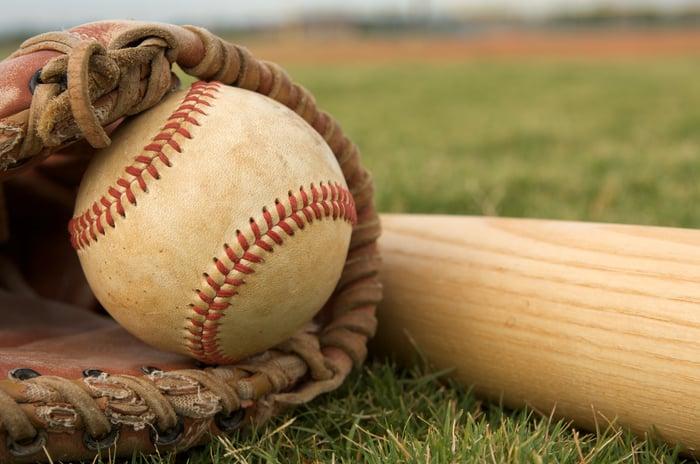 A baseball resting in a baseball mitt next to a bat in the grass.