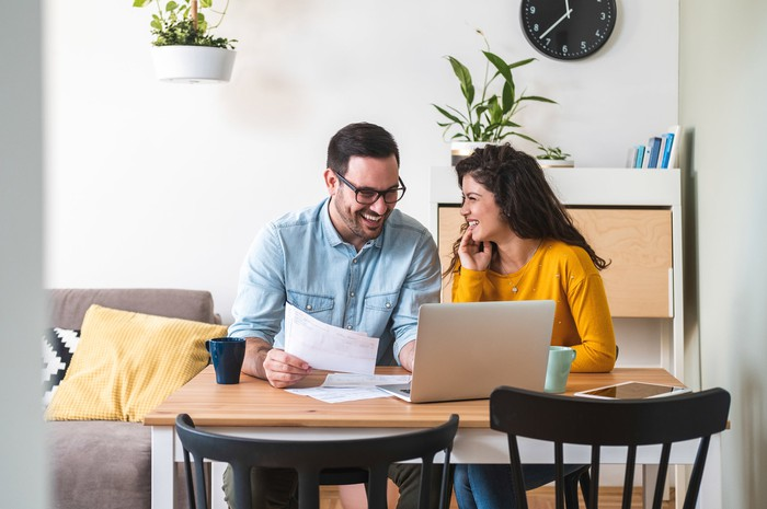 Smiling couple sitting at table reviewing papers