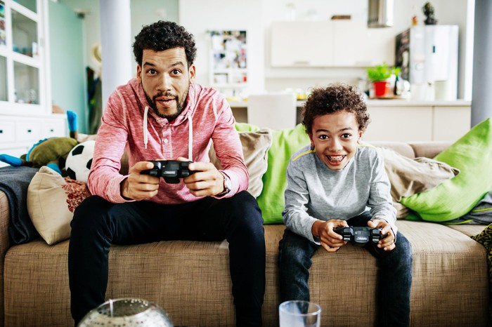 A father and son playing video games while seated next to each other on a couch.