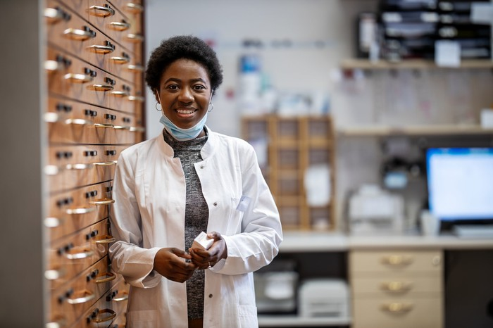 Female pharmacist in a white coat holds a medicine bottle while leaning against a wall of medicine drawers and files.