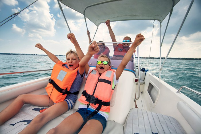 A family on a boat with kids sitting up front wearing life vests and their hands in the air.