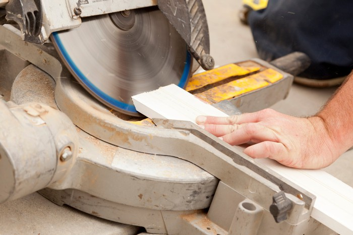 Some hands are using a miter saw.