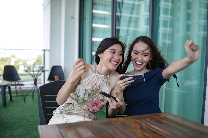 Two young girls clenching celebratory fists while playing with a smartphone on a balcony.