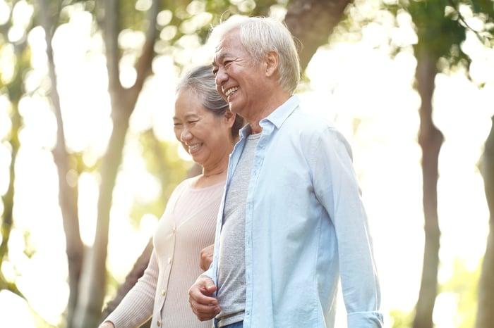 Smiling older couple walking side by side