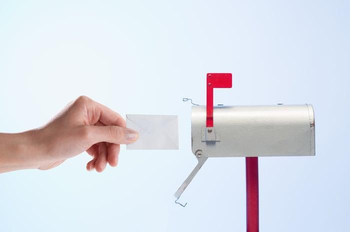 Une main atteignant une lettre dans une petite boîte aux lettres.