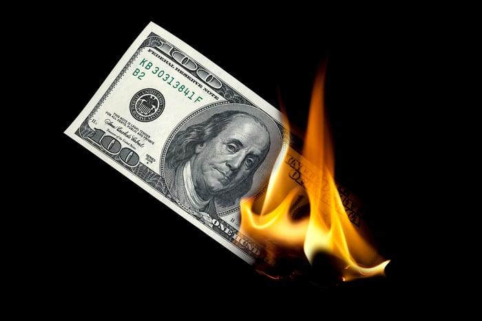 A $100 bill on fire.