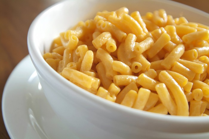 A bowl of macaroni and cheese on a table.