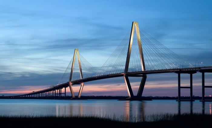 A long bridge over water at night.