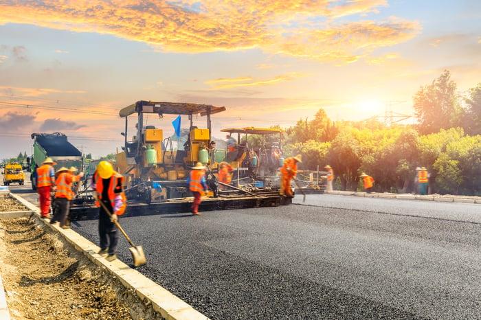 A construction crew works on a black asphalt road.
