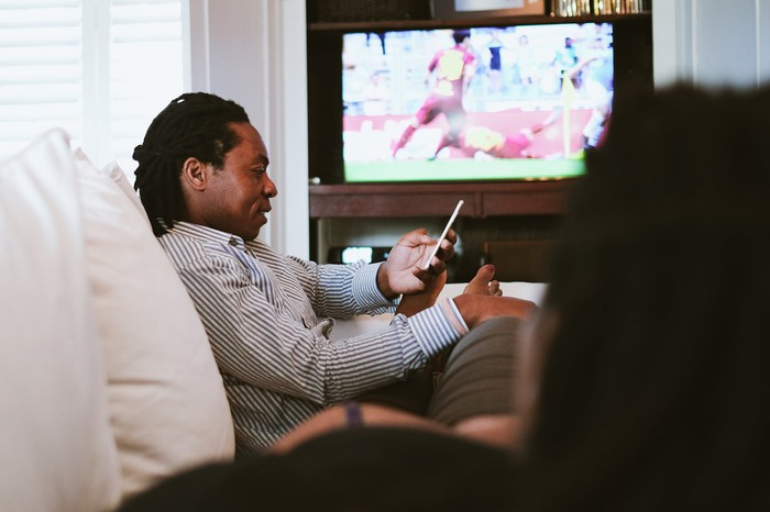 Man watching a soccer match while on his smartphone.