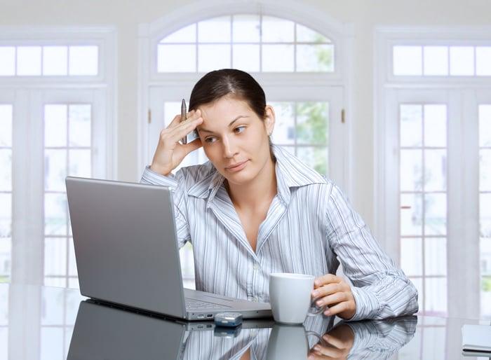 Investor pondering in front of her computer.