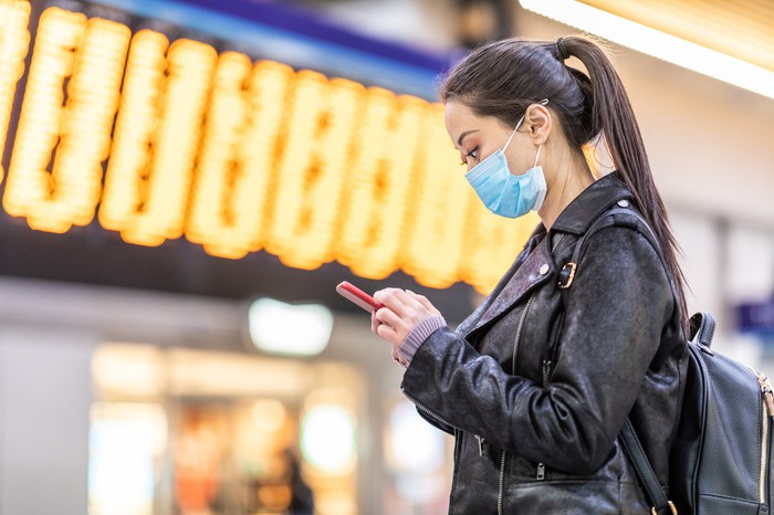 Woman in protective mask using a smartphone.
