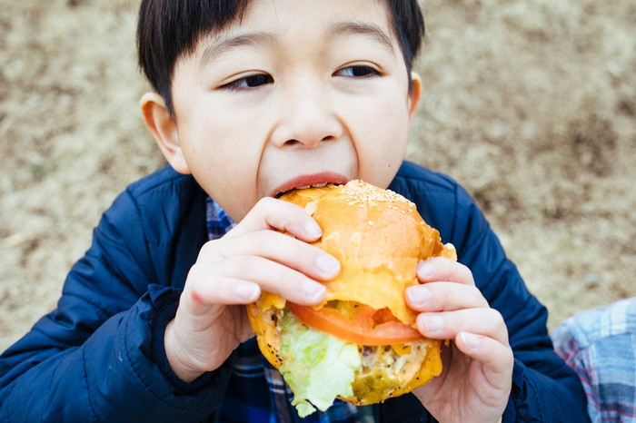 A child about to bite into a hamburger.