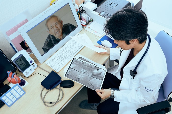 A male doctor talks to mature male patients during a video chat while reviewing medical scan material.
