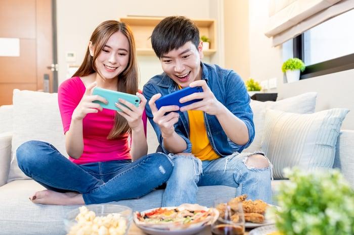 Deux enfants jouant sur leurs smartphones.