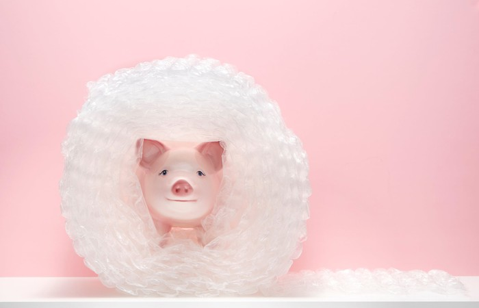 Piggy bank wrapped in bubble wrap in front of a pink background.