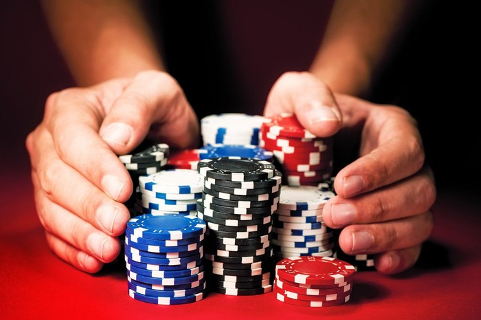 Two hands pushing piles of poker chips forward.
