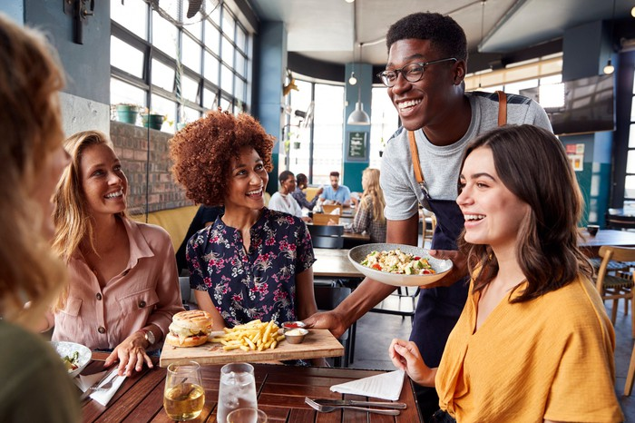 Un groupe de personnes sourit alors qu'un serveur leur donne leur nourriture dans un restaurant.