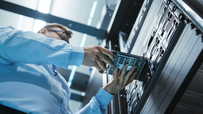 An engineer placing a hard drive into a data center server tower.