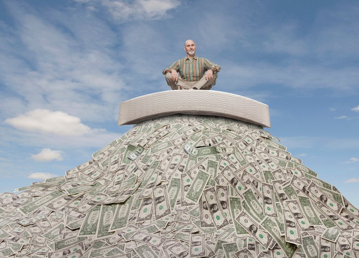 Retiree sitting on top of a large pile of cash