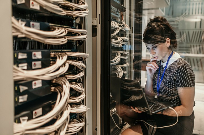 Young woman inside a data center monitoring servers on her laptop.
