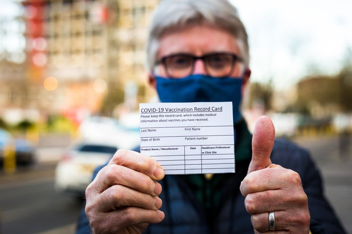 A man holds up a coronavirus vaccine record card while giving a thumbs up.
