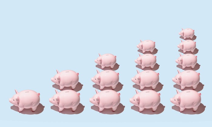 Piggy banks lined up in stacks of increasing height.