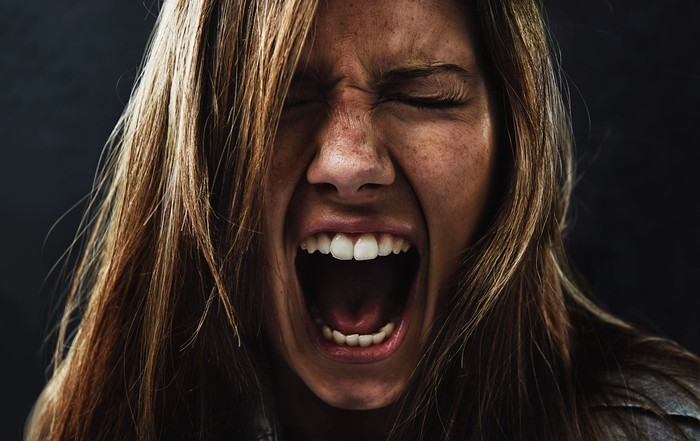 A panicked woman screams against a black background.