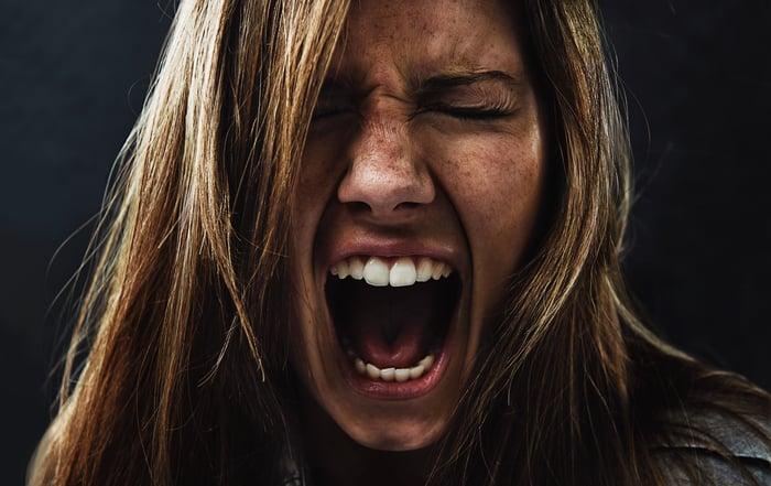 Une femme paniquée hurle sur un fond noir.