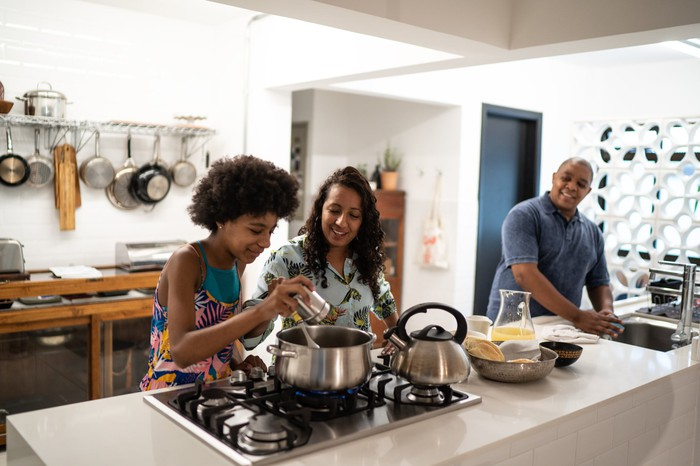 Child adding spice to pot while cooking with parents