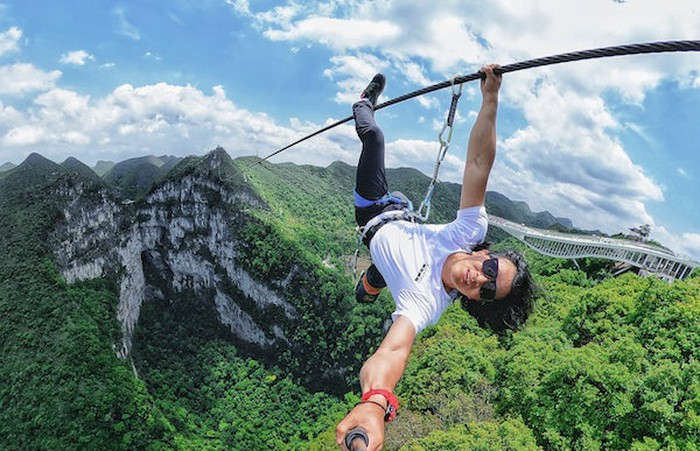 A daredevil takes a selfie while dangling from a steel cable above a wide, deep mountain gorge.