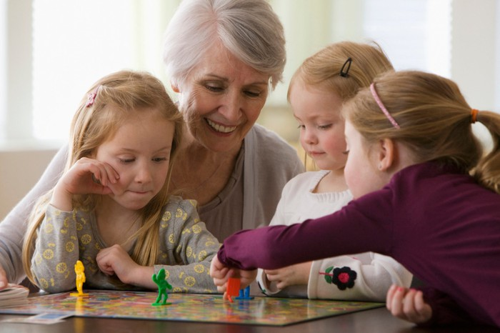 A woman playing a board game with her grandchildren.