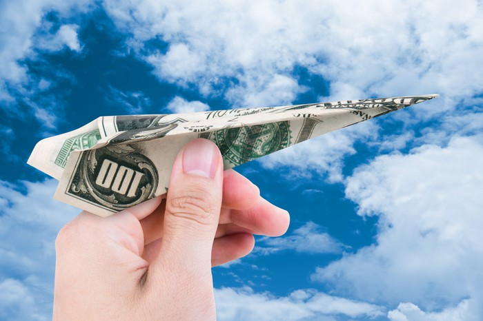 A hand holding a one hundred-dollar bill folded up as a paper airplane against a cloudy sky.