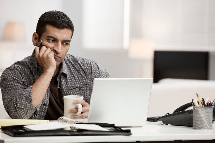 Man staring at laptop with confused expression