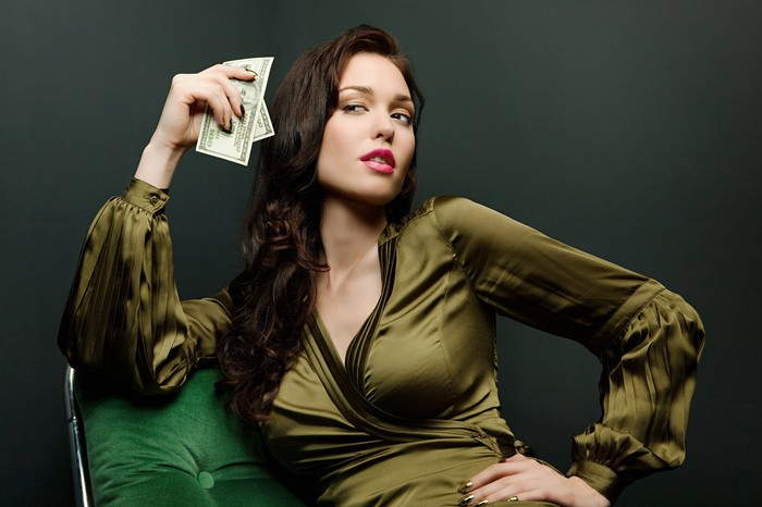 A young woman holding dollar bills.