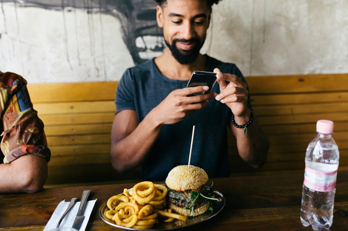A guy taking a picture of a burger with his phone.