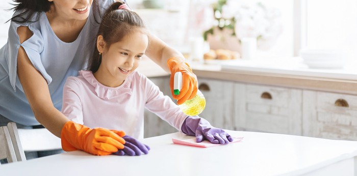 A mother and child clean a countertop together.