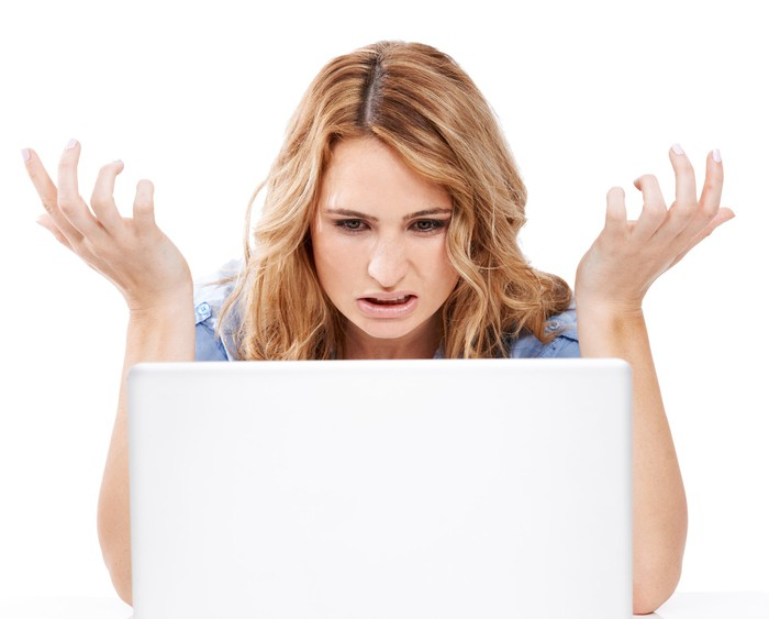 A frustrated lady throws her hands up while staring at her computer.