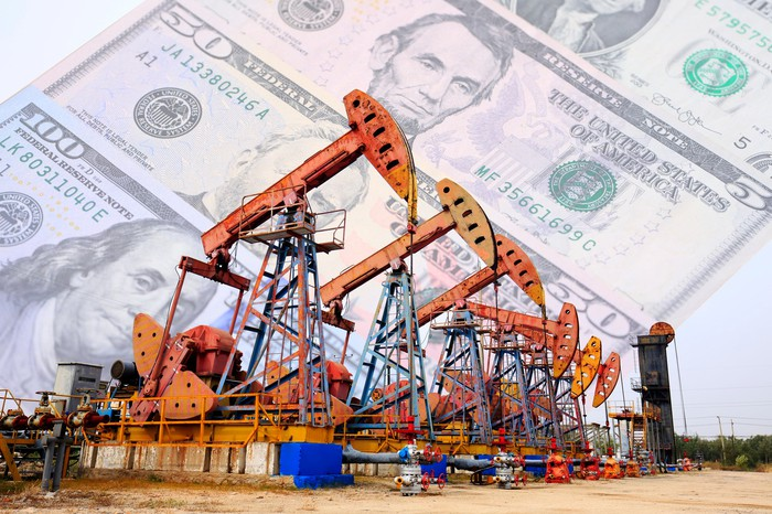 A row of oil pumps with cash in the background.