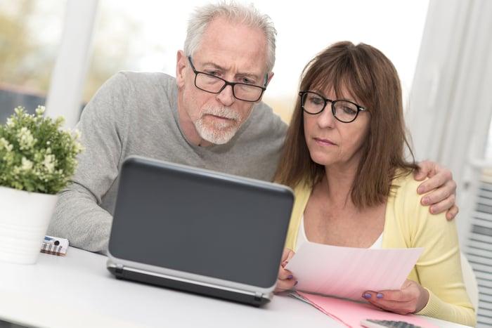 Homme plus âgé et femme avec des expressions sérieuses tout en regardant un ordinateur portable
