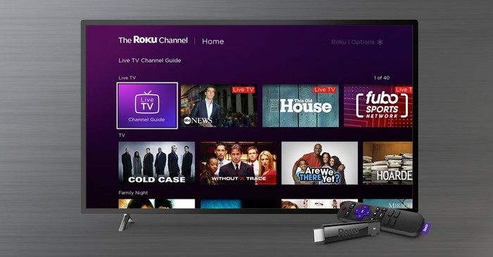 The Roku Channel home screen on a TV with a Roku Stick and remote in front of it